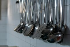 Iron spoons in a restaurant kitchen royalty free stock photography