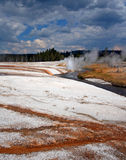 Iron Spring Creek flowing past Cliff Geyser in Black Sand Geyser Basin in Yellowstone National Park in Wyoming USA Royalty Free Stock Photos