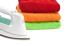 Iron and stacked colorful towels. Stock Photography