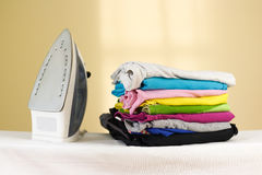 Iron stands with stacks of ironed colored linen. Pile of clothes Stock Photo