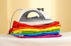 Iron stands with stacks of ironed colored linen. Pile of clothes Stock Photos