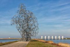 Iron statue of man on dam in Lelystad, The Netherlands. Iron statue of a man sitting on his heels on an enclosure dam in Lelystad, The Netherlands stock images