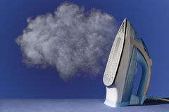 Iron with steam. Hot vertical new iron throws cloud of white steam on blue background Stock Image