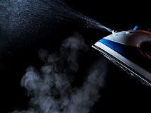 Iron with steam and water stream  isolated on a black Stock Images