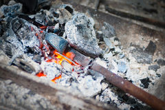 Iron stick in hammer furnace Royalty Free Stock Photography