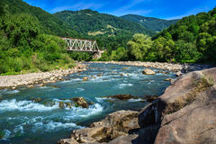 Iron and stone on mountain river. Iron Bridge and a giant stone on the opposite side of the river in the mountains Stock Images