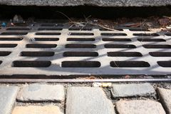 Iron Storm Drain with Bricks and Debris. An iron storm drain on a city street that has waste clogged in it. This image has all thirds for text or motion graphics royalty free stock images