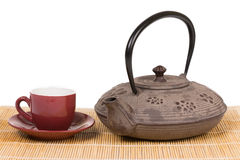 Iron teapot with red cup of tea on wooden mat. Stock Image