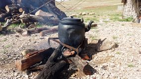 Iron teapot sits on open fire heating water.  stock video