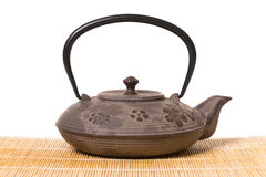 Iron teapot on wooden mat. Royalty Free Stock Images