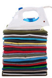 Iron on top of folded tee-shirts in a pile. Isolated on white background Stock Image