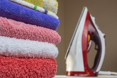 Iron and towels close up. Ironing of clean linen stock photography