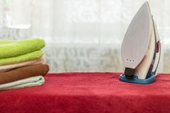 Iron with towels on ironing board Stock Photography