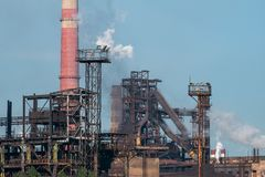 Iron tower constructions and pipes with smog of metallurgical plant as industrial background. Pollution from heavy industry. Concept royalty free stock image