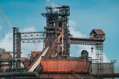 Iron tower constructions and pipes with smog of metallurgical plant as industrial background. Pollution from heavy industry. Concept stock photo
