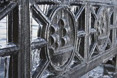 Iron transformed into ice. A fragment of iron fence at the rim of embankment soaked in water during storm and frozen Royalty Free Stock Images