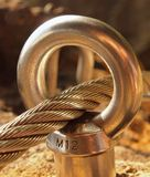 Iron twisted rope fixed in block by screws snap hooks. Detail of rope end anchored into rock. Iron twisted rope fixed in block by screws snap hooks. Detail of stock photo
