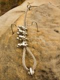 Iron twisted rope fixed in block by screws snap hooks. Detail of rope end anchored into sandstone rock Stock Photo