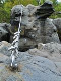 Iron twisted rope fixed in block by screws snaphooks. Detail of end of the anchored  rope Royalty Free Stock Photography