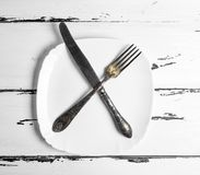 Iron vintage fork with knife lying on a blank white square plate Royalty Free Stock Photo