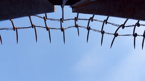 Iron wall with barbed wire Stock Image