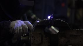 Iron welding with bright light and smoke at manufacturing. Clip. Industrial worker man at the factory welding close up. By arc stock image