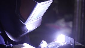 Iron welding with bright light and smoke at manufacturing. Clip. Industrial worker man at the factory welding close up. By arc stock photography