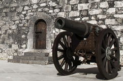 Iron wheel cannon close up. Cannon close to a vintage fortress door Stock Photo