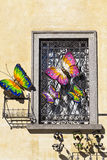 Iron window with colourful butterflies on yellow wall Royalty Free Stock Photos