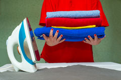 Iron and woman's hands holding the pile of colorful clothes Royalty Free Stock Photos