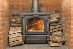 Wood Burning Stove. Metal wood burner in brick fireplace surrounded by logs Stock Photography