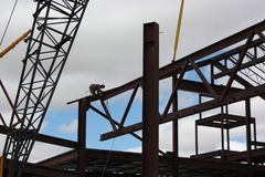 Iron Worker Guides Truss-Joist into Position. An iron worker guides a large truss-joist into position on a steel beam; The worker is tethered by lanyard to a Stock Photography