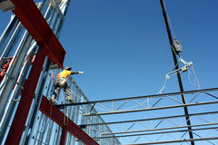 Iron Worker Setting Bar Joist. An iron worker in control of a bar joist release checks with his workmate on the other end before releasing the bar joist Stock Photo