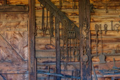 Iron working and rusted tools and chains hanging on an old woode Royalty Free Stock Image