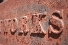 Rusty Iron Works. The word WORKS in rusty cast iron machinery stock photos