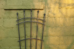 Iron works on a concrete wall. Iron lances on a green concrete wall royalty free stock photography
