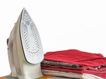 Iron and wrinkled clothes standing beside stock image