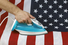 Ironed Crumpled US flag. Conceptual photography male hand with the included iron irons American Stripes Royalty Free Stock Photos