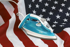 Ironed Crumpled US flag. Conceptual photography male hand with the included iron irons American Stripes Royalty Free Stock Photography