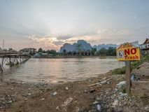Nam Song River, Laos. Ironic anti-trash sign on the banks of the Nam Song River. Sun setting over impressive limestone mountains in the background. Vang Vieng royalty free stock image