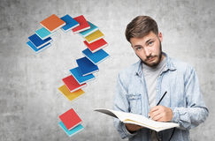 Ironical guy in jeans shirt and a book question Royalty Free Stock Images