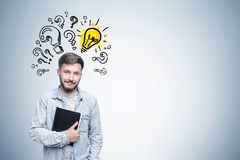 Ironical guy in jeans shirt, question marks bulb Stock Photos