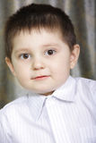 Ironical smile. Portrait of a kid looking stright to camera with ironical smile Royalty Free Stock Photos
