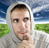 Ironically pensive man. Hooded man thinking with a finger in his mouth and looking away Stock Photography