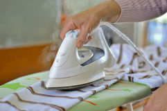 Ironing. A woman ironing a sweater Stock Photos