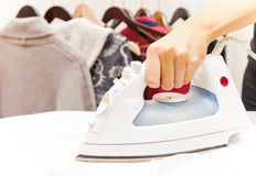 Ironing. Hand holding iron in hand against background with cloths on hangers Royalty Free Stock Image