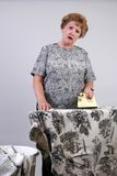 Ironing. A woman before a huge basket of laundry irons her clothes Royalty Free Stock Photo