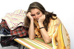 Ironing. Young woman very listless at an ironing board full of shirts Stock Photos