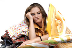 Ironing. Young woman very listless at an ironing board full of shirts Royalty Free Stock Photo