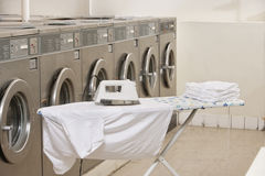Ironing board with washing machines in Laundromat Stock Photos